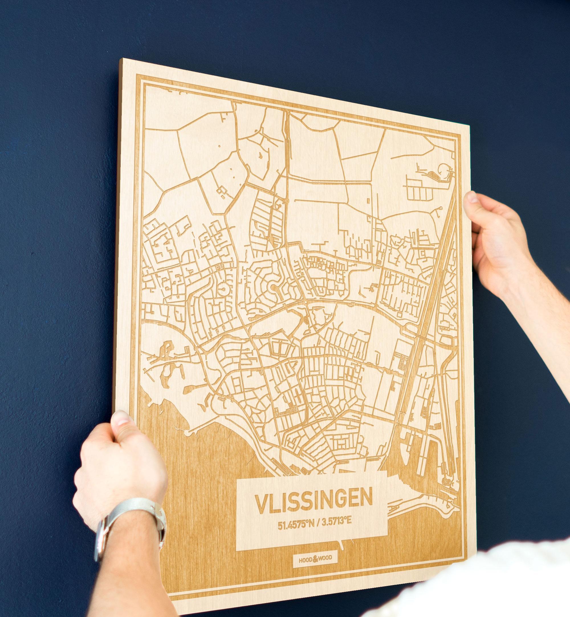 Een man hangt de houten plattegrond Vlissingen aan zijn blauwe muur ter decoratie. Je ziet alleen zijn handen de kaart van deze speciale in Zeeland vasthouden.