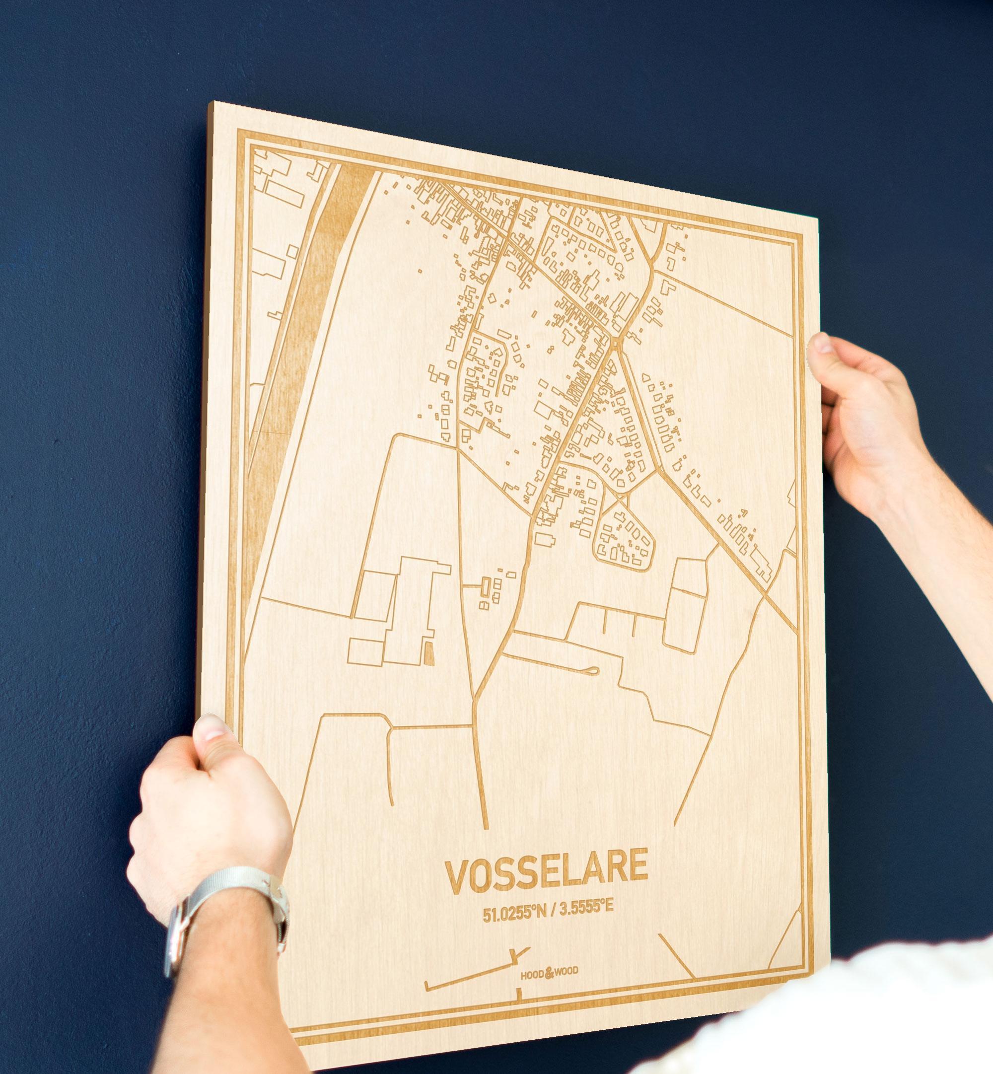 Een man hangt de houten plattegrond Vosselare aan zijn blauwe muur ter decoratie. Je ziet alleen zijn handen de kaart van deze stijlvolle in Oost-Vlaanderen  vasthouden.