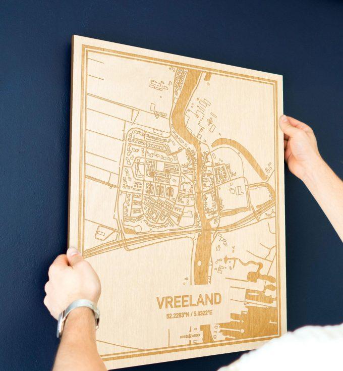 Een man hangt de houten plattegrond Vreeland aan zijn blauwe muur ter decoratie. Je ziet alleen zijn handen de kaart van deze moderne in Utrecht vasthouden.
