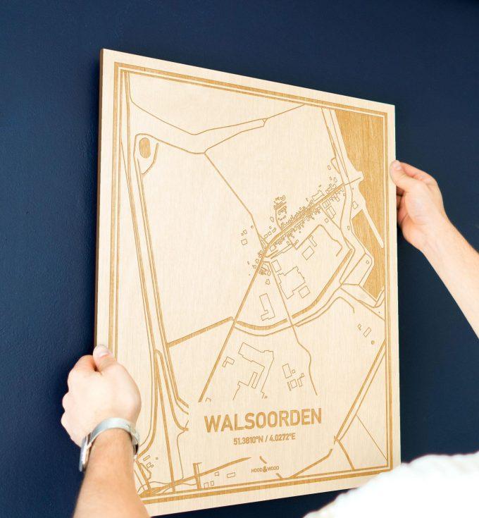 Een man hangt de houten plattegrond Walsoorden aan zijn blauwe muur ter decoratie. Je ziet alleen zijn handen de kaart van deze stijlvolle in Zeeland vasthouden.