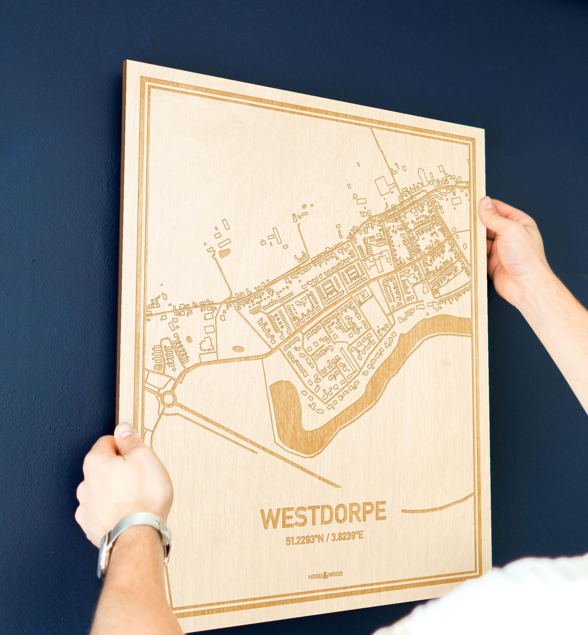 Een man hangt de houten plattegrond Westdorpe aan zijn blauwe muur ter decoratie. Je ziet alleen zijn handen de kaart van deze stijlvolle in Zeeland vasthouden.