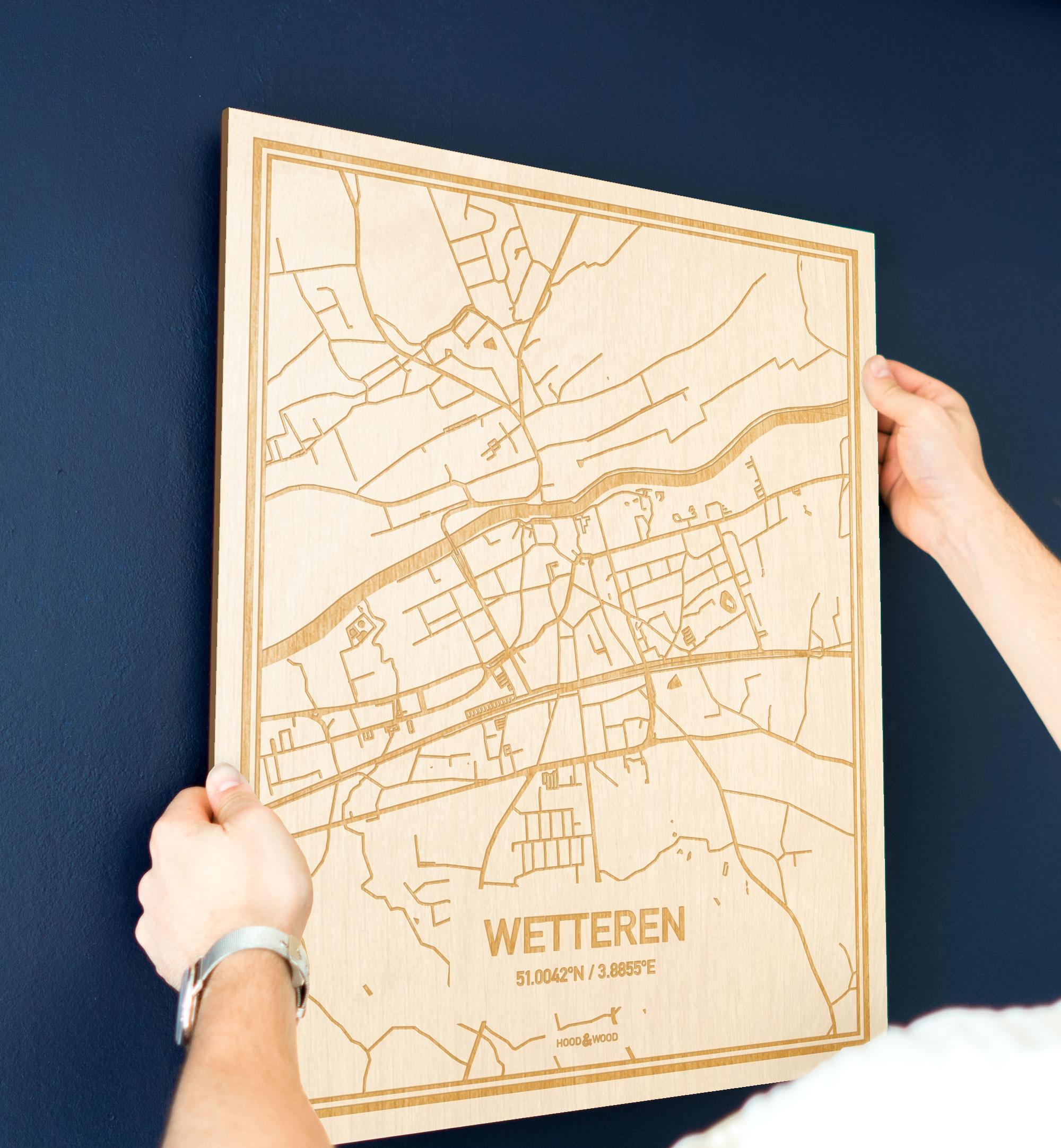 Een man hangt de houten plattegrond Wetteren aan zijn blauwe muur ter decoratie. Je ziet alleen zijn handen de kaart van deze prachtige in Oost-Vlaanderen  vasthouden.