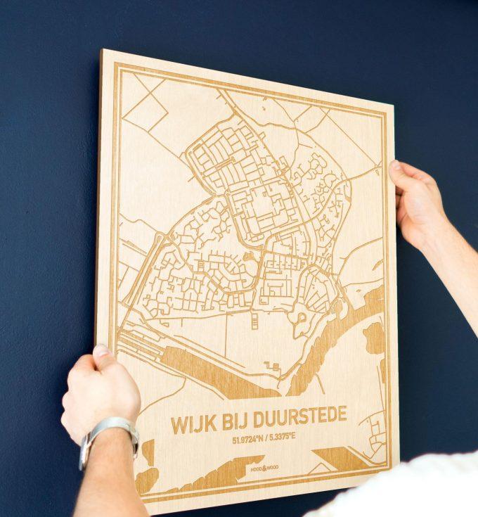 Een man hangt de houten plattegrond Wijk bij Duurstede aan zijn blauwe muur ter decoratie. Je ziet alleen zijn handen de kaart van deze speciale in Utrecht vasthouden.