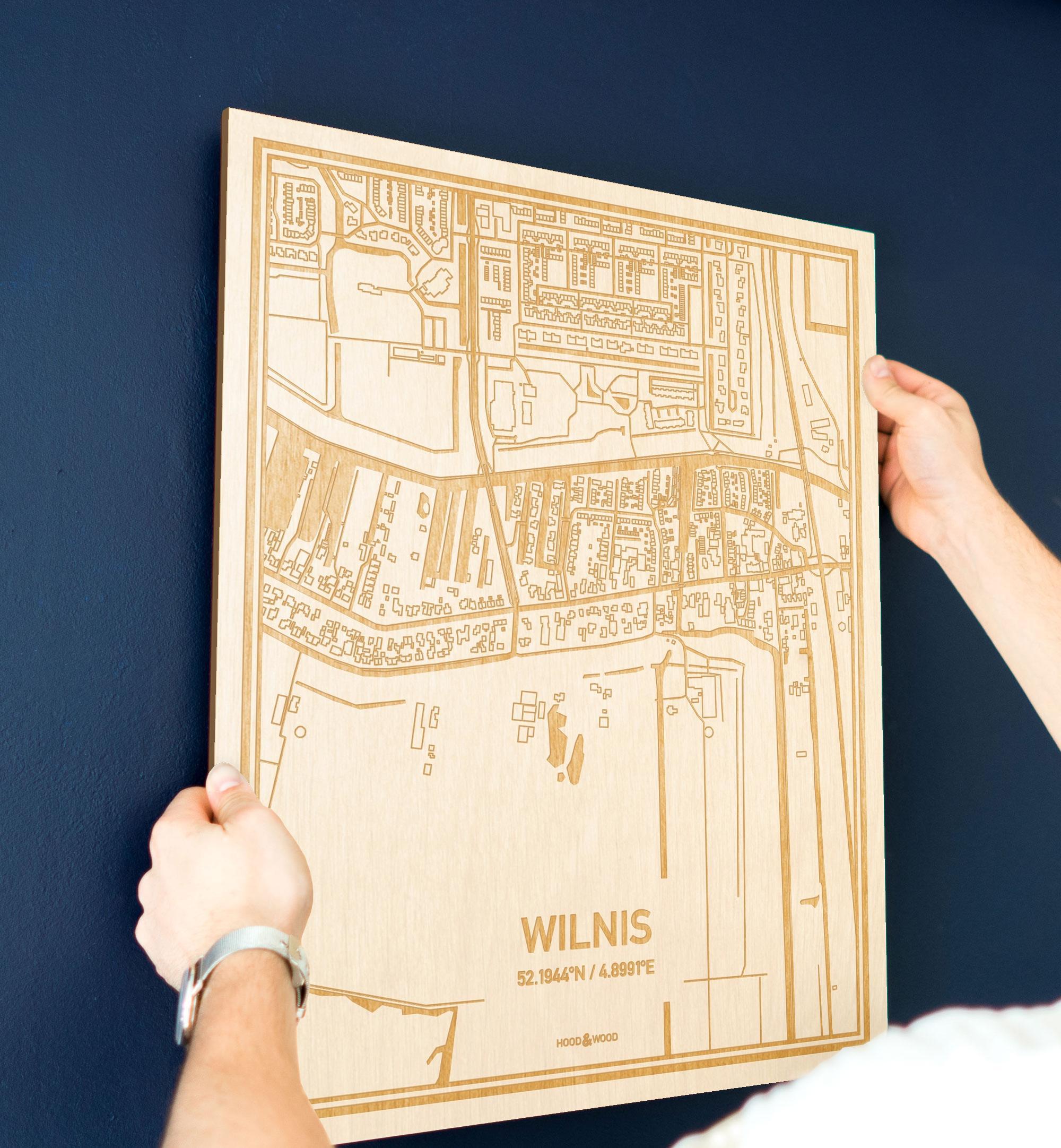 Een man hangt de houten plattegrond Wilnis aan zijn blauwe muur ter decoratie. Je ziet alleen zijn handen de kaart van deze bijzondere in Utrecht vasthouden.