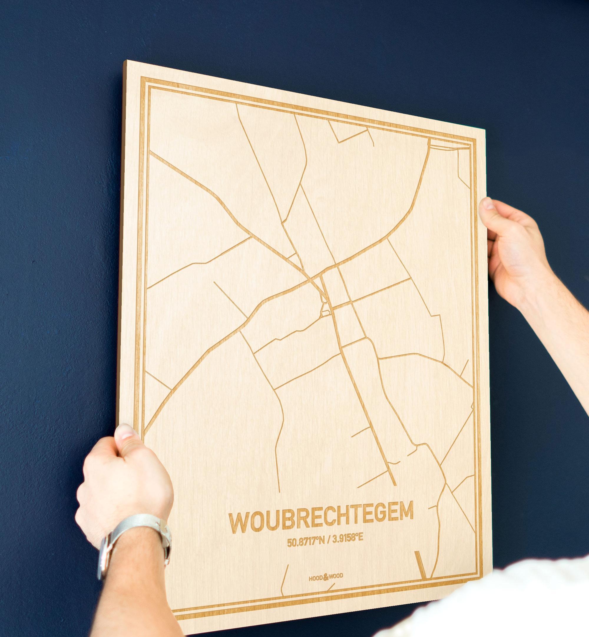 Een man hangt de houten plattegrond Woubrechtegem aan zijn blauwe muur ter decoratie. Je ziet alleen zijn handen de kaart van deze moderne in Oost-Vlaanderen  vasthouden.