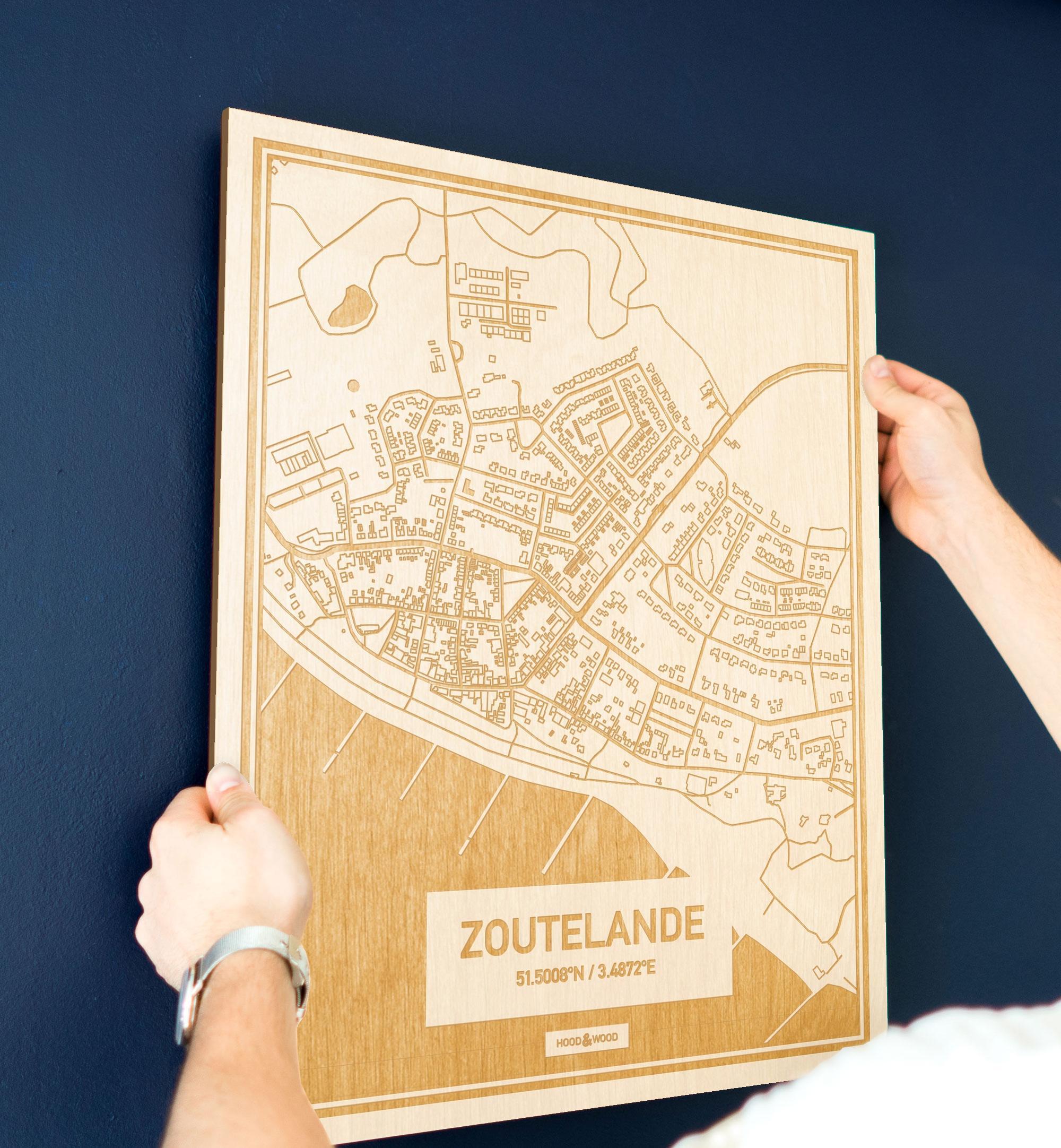 Een man hangt de houten plattegrond Zoutelande aan zijn blauwe muur ter decoratie. Je ziet alleen zijn handen de kaart van deze verrassende in Zeeland vasthouden.