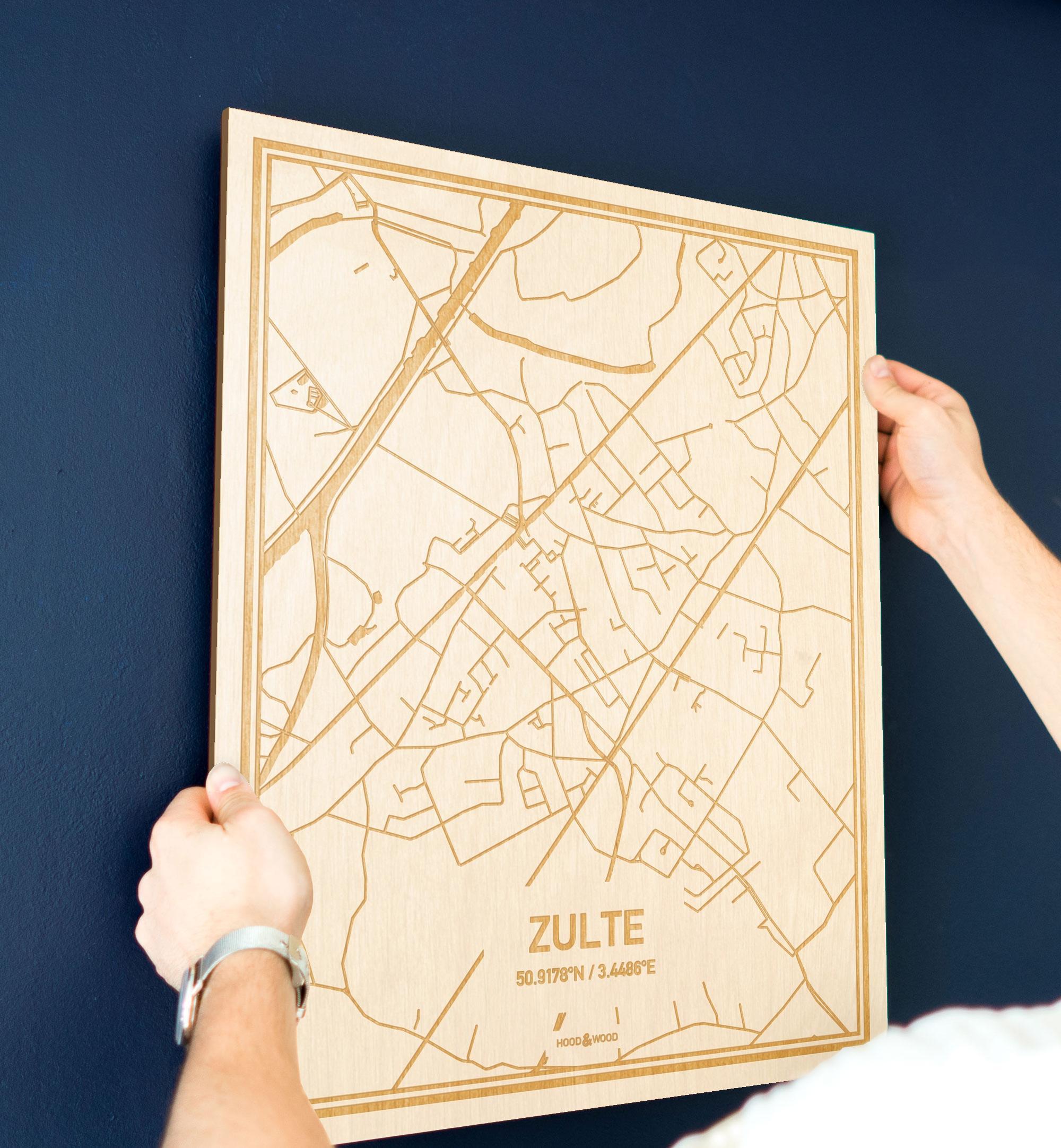 Een man hangt de houten plattegrond Zulte aan zijn blauwe muur ter decoratie. Je ziet alleen zijn handen de kaart van deze speciale in Oost-Vlaanderen  vasthouden.