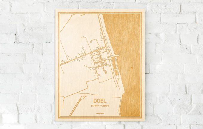 De kaart Doel aan een witte bakstenen muur. Prachtige persoonlijke muurdecoratie. Lasers graveren Doel haar straten, buurten en huizen waardoor een unieke plaats in Oost-Vlaanderen  mooi in kaart gebracht wordt.