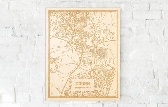 De kaart Doorn aan een witte bakstenen muur. Prachtige persoonlijke muurdecoratie. Lasers graveren Doorn haar straten, buurten en huizen waardoor een schitterende plaats in Utrecht mooi in kaart gebracht wordt.