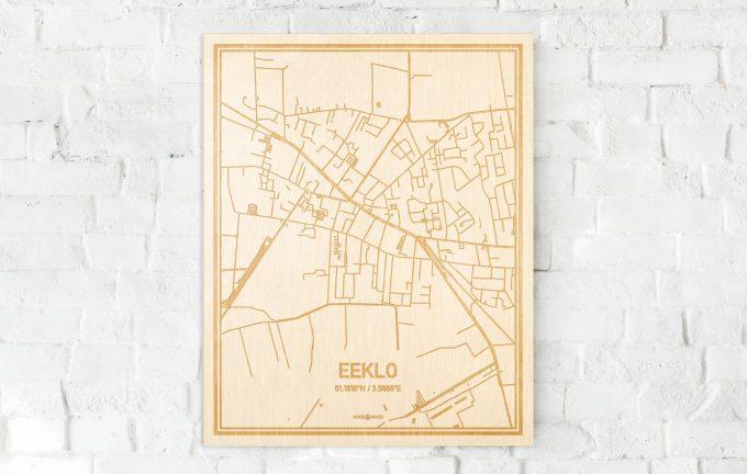De kaart Eeklo aan een witte bakstenen muur. Prachtige persoonlijke muurdecoratie. Lasers graveren Eeklo haar straten, buurten en huizen waardoor een bijzondere plaats in Oost-Vlaanderen  mooi in kaart gebracht wordt.
