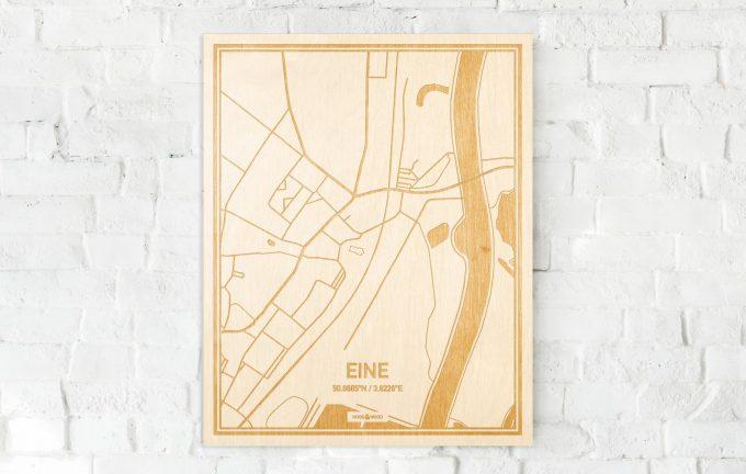 De kaart Eine aan een witte bakstenen muur. Prachtige persoonlijke muurdecoratie. Lasers graveren Eine haar straten, buurten en huizen waardoor een verrassende plaats in Oost-Vlaanderen  mooi in kaart gebracht wordt.