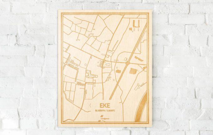 De kaart Eke aan een witte bakstenen muur. Prachtige persoonlijke muurdecoratie. Lasers graveren Eke haar straten, buurten en huizen waardoor een bijzondere plaats in Oost-Vlaanderen  mooi in kaart gebracht wordt.