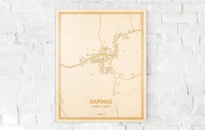 De kaart Gapinge aan een witte bakstenen muur. Prachtige persoonlijke muurdecoratie. Lasers graveren Gapinge haar straten, buurten en huizen waardoor een bijzondere plaats in Zeeland mooi in kaart gebracht wordt.
