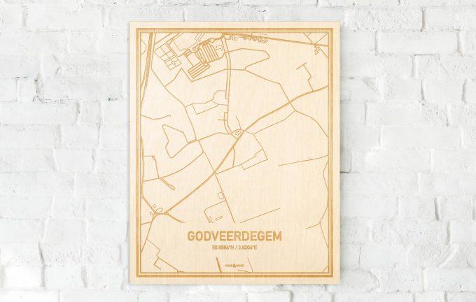 De kaart Godveerdegem aan een witte bakstenen muur. Prachtige persoonlijke muurdecoratie. Lasers graveren Godveerdegem haar straten, buurten en huizen waardoor een unieke plaats in Oost-Vlaanderen  mooi in kaart gebracht wordt.