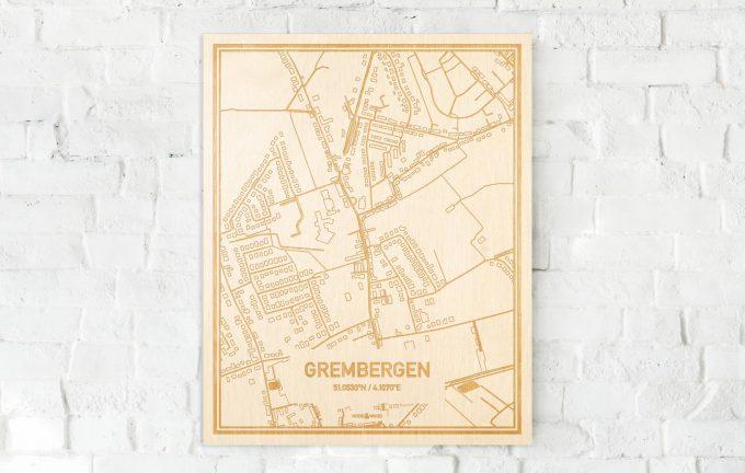 De kaart Grembergen aan een witte bakstenen muur. Prachtige persoonlijke muurdecoratie. Lasers graveren Grembergen haar straten, buurten en huizen waardoor een bijzondere plaats in Oost-Vlaanderen  mooi in kaart gebracht wordt.