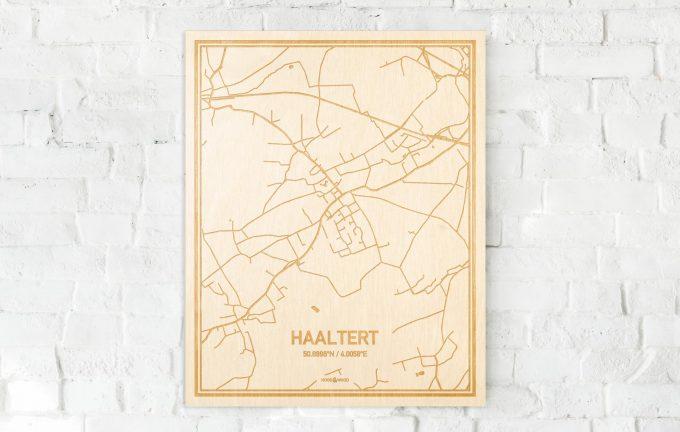 De kaart Haaltert aan een witte bakstenen muur. Prachtige persoonlijke muurdecoratie. Lasers graveren Haaltert haar straten, buurten en huizen waardoor een bijzondere plaats in Oost-Vlaanderen  mooi in kaart gebracht wordt.
