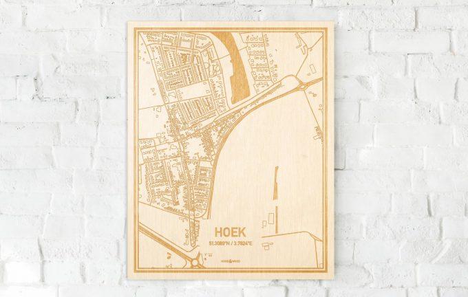 De kaart Hoek aan een witte bakstenen muur. Prachtige persoonlijke muurdecoratie. Lasers graveren Hoek haar straten, buurten en huizen waardoor een prachtige plaats in Zeeland mooi in kaart gebracht wordt.