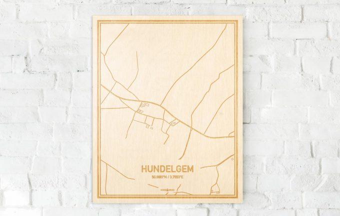 De kaart Hundelgem aan een witte bakstenen muur. Prachtige persoonlijke muurdecoratie. Lasers graveren Hundelgem haar straten, buurten en huizen waardoor een speciale plaats in Oost-Vlaanderen  mooi in kaart gebracht wordt.