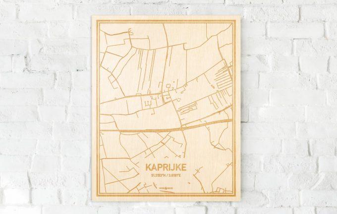 De kaart Kaprijke aan een witte bakstenen muur. Prachtige persoonlijke muurdecoratie. Lasers graveren Kaprijke haar straten, buurten en huizen waardoor een speciale plaats in Oost-Vlaanderen  mooi in kaart gebracht wordt.