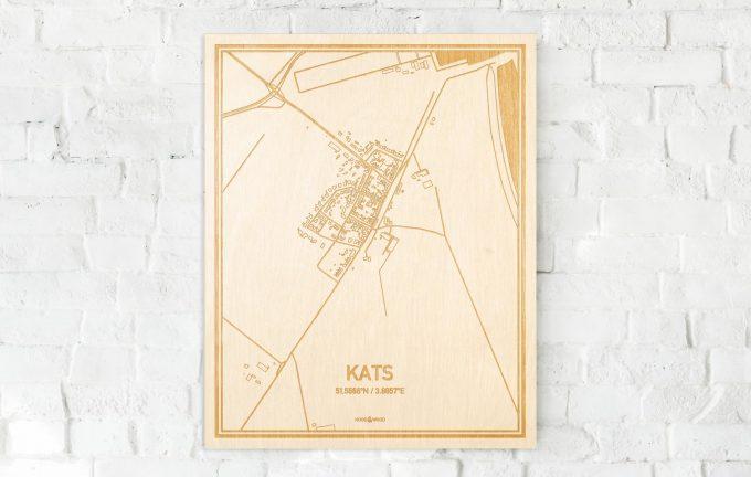 De kaart Kats aan een witte bakstenen muur. Prachtige persoonlijke muurdecoratie. Lasers graveren Kats haar straten, buurten en huizen waardoor een originele plaats in Zeeland mooi in kaart gebracht wordt.