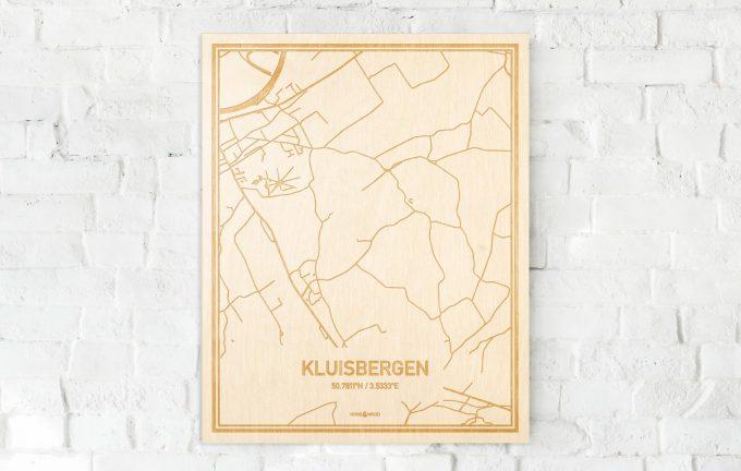 De kaart Kluisbergen aan een witte bakstenen muur. Prachtige persoonlijke muurdecoratie. Lasers graveren Kluisbergen haar straten, buurten en huizen waardoor een verrassende plaats in Oost-Vlaanderen  mooi in kaart gebracht wordt.