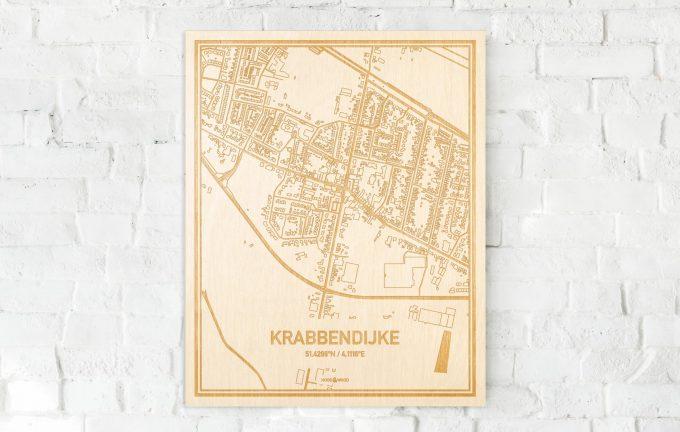 De kaart Krabbendijke aan een witte bakstenen muur. Prachtige persoonlijke muurdecoratie. Lasers graveren Krabbendijke haar straten, buurten en huizen waardoor een moderne plaats in Zeeland mooi in kaart gebracht wordt.