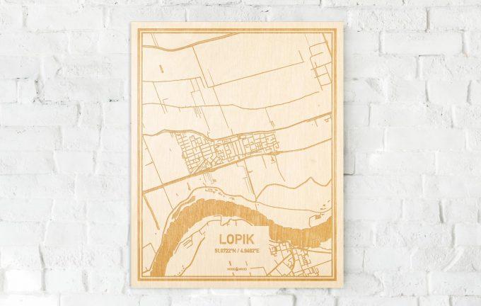 De kaart Lopik aan een witte bakstenen muur. Prachtige persoonlijke muurdecoratie. Lasers graveren Lopik haar straten, buurten en huizen waardoor een originele plaats in Utrecht mooi in kaart gebracht wordt.