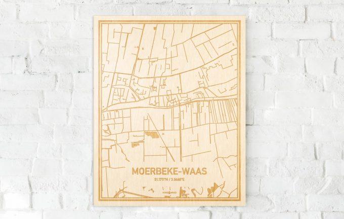 De kaart Moerbeke-Waas aan een witte bakstenen muur. Prachtige persoonlijke muurdecoratie. Lasers graveren Moerbeke-Waas haar straten, buurten en huizen waardoor een originele plaats in Oost-Vlaanderen  mooi in kaart gebracht wordt.
