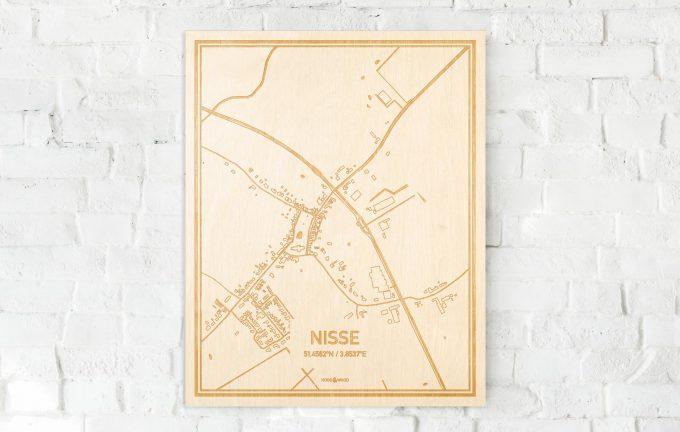 De kaart Nisse aan een witte bakstenen muur. Prachtige persoonlijke muurdecoratie. Lasers graveren Nisse haar straten, buurten en huizen waardoor een unieke plaats in Zeeland mooi in kaart gebracht wordt.