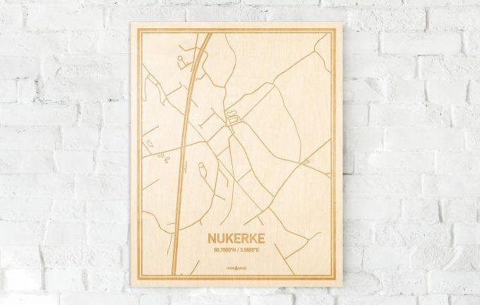 De kaart Nukerke aan een witte bakstenen muur. Prachtige persoonlijke muurdecoratie. Lasers graveren Nukerke haar straten, buurten en huizen waardoor een verrassende plaats in Oost-Vlaanderen  mooi in kaart gebracht wordt.