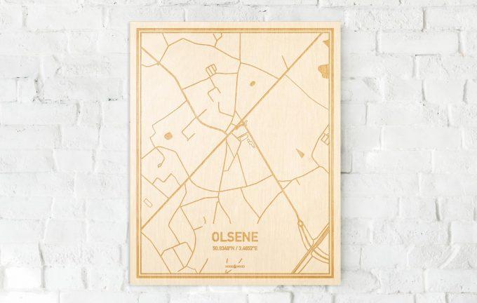 De kaart Olsene aan een witte bakstenen muur. Prachtige persoonlijke muurdecoratie. Lasers graveren Olsene haar straten, buurten en huizen waardoor een unieke plaats in Oost-Vlaanderen  mooi in kaart gebracht wordt.