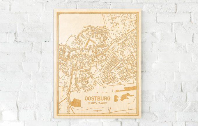 De kaart Oostburg aan een witte bakstenen muur. Prachtige persoonlijke muurdecoratie. Lasers graveren Oostburg haar straten, buurten en huizen waardoor een opvallende plaats in Zeeland mooi in kaart gebracht wordt.