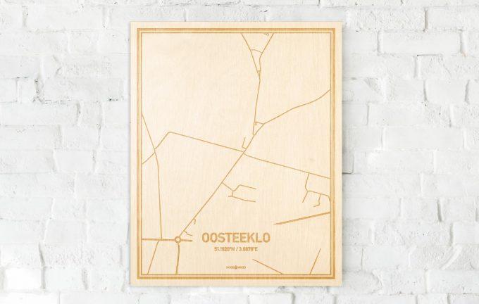 De kaart Oosteeklo aan een witte bakstenen muur. Prachtige persoonlijke muurdecoratie. Lasers graveren Oosteeklo haar straten, buurten en huizen waardoor een schitterende plaats in Oost-Vlaanderen  mooi in kaart gebracht wordt.