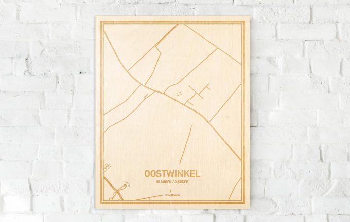 De kaart Oostwinkel aan een witte bakstenen muur. Prachtige persoonlijke muurdecoratie. Lasers graveren Oostwinkel haar straten, buurten en huizen waardoor een unieke plaats in Oost-Vlaanderen  mooi in kaart gebracht wordt.