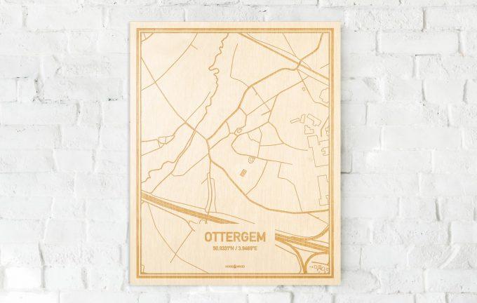 De kaart Ottergem aan een witte bakstenen muur. Prachtige persoonlijke muurdecoratie. Lasers graveren Ottergem haar straten, buurten en huizen waardoor een unieke plaats in Oost-Vlaanderen  mooi in kaart gebracht wordt.