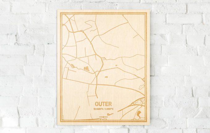 De kaart Outer aan een witte bakstenen muur. Prachtige persoonlijke muurdecoratie. Lasers graveren Outer haar straten, buurten en huizen waardoor een bijzondere plaats in Oost-Vlaanderen  mooi in kaart gebracht wordt.