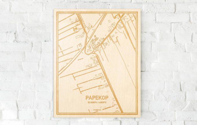 De kaart Papekop aan een witte bakstenen muur. Prachtige persoonlijke muurdecoratie. Lasers graveren Papekop haar straten, buurten en huizen waardoor een moderne plaats in Utrecht mooi in kaart gebracht wordt.