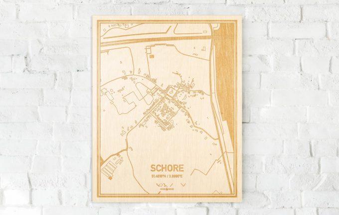 De kaart Schore aan een witte bakstenen muur. Prachtige persoonlijke muurdecoratie. Lasers graveren Schore haar straten, buurten en huizen waardoor een speciale plaats in Zeeland mooi in kaart gebracht wordt.
