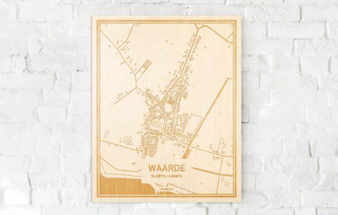 De kaart Waarde aan een witte bakstenen muur. Prachtige persoonlijke muurdecoratie. Lasers graveren Waarde haar straten, buurten en huizen waardoor een prachtige plaats in Zeeland mooi in kaart gebracht wordt.