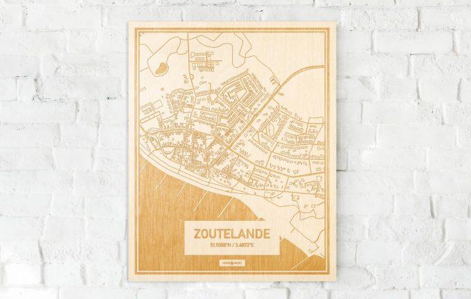 De kaart Zoutelande aan een witte bakstenen muur. Prachtige persoonlijke muurdecoratie. Lasers graveren Zoutelande haar straten, buurten en huizen waardoor een speciale plaats in Zeeland mooi in kaart gebracht wordt.